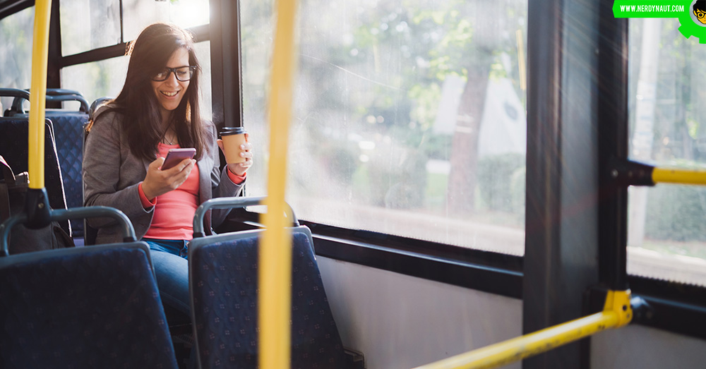 girl using phone while travelling in a bus