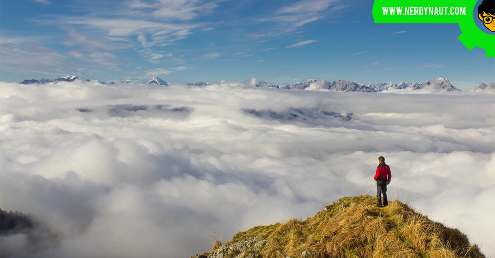 Man Standing on Mountain Against Sky after Hiking